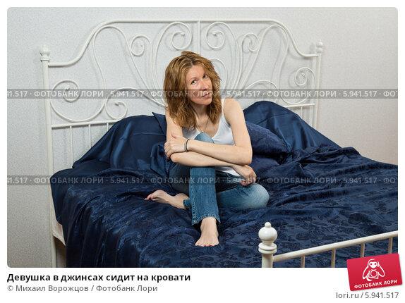 Купить «Девушка в джинсах сидит на кровати», фото № 5941517, снято 12 июня 2013 г. (c) Михаил Ворожцов / Фотобанк Лори