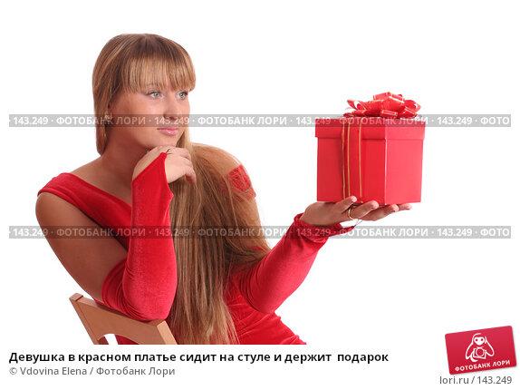 Девушка в красном платье сидит на стуле и держит  подарок, фото № 143249, снято 15 ноября 2007 г. (c) Vdovina Elena / Фотобанк Лори