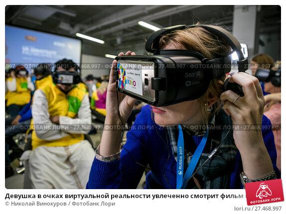Купить «Девушка в очках виртуальной реальности увлеченно смотрит фильм в современном инотеатре виртуальной реальности в городе Сочи, Россия», фото № 27468997, снято 16 октября 2017 г. (c) Николай Винокуров / Фотобанк Лори