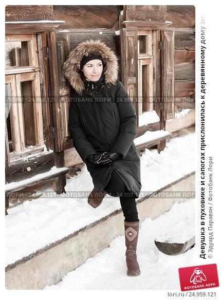Девушка в пуховике и сапогах прислонилась к деревянному дому зимой и с хитрой улыбкой смотрит в сторону, фото № 24959121, снято 7 января 2011 г. (c) Эдуард Паравян / Фотобанк Лори