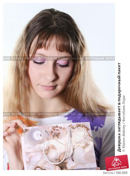 Купить «Девушка заглядывает в подарочный пакет», фото № 166569, снято 16 ноября 2007 г. (c) Efanov Aleksey / Фотобанк Лори