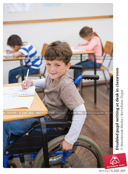 Купить «Disabled pupil writing at desk in classroom», фото № 6500365, снято 11 мая 2014 г. (c) Wavebreak Media / Фотобанк Лори