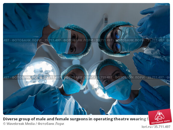 Diverse group of male and female surgeons in operating theatre wearing face masks performing surgery. Стоковое фото, агентство Wavebreak Media / Фотобанк Лори