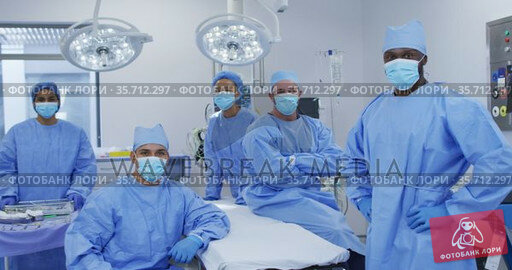 Diverse male and female doctors wearing face masks standing in operating theatre smiling to camera. Стоковое видео, агентство Wavebreak Media / Фотобанк Лори