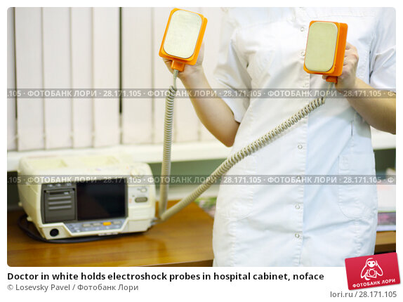 Купить «Doctor in white holds electroshock probes in hospital cabinet, noface», фото № 28171105, снято 20 ноября 2015 г. (c) Losevsky Pavel / Фотобанк Лори