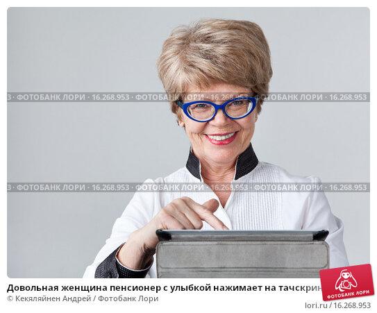 Купить «Довольная женщина пенсионер с улыбкой нажимает на тачскрин планшета», фото № 16268953, снято 13 декабря 2015 г. (c) Кекяляйнен Андрей / Фотобанк Лори
