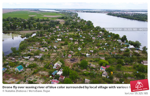 Drone fly over waving river of blue color surrounded by local village with various buildings and Wetland and marsh habitat with a reedbed of Common Reed aerial view. Редакционное фото, фотограф Nataliia Zhekova / Фотобанк Лори