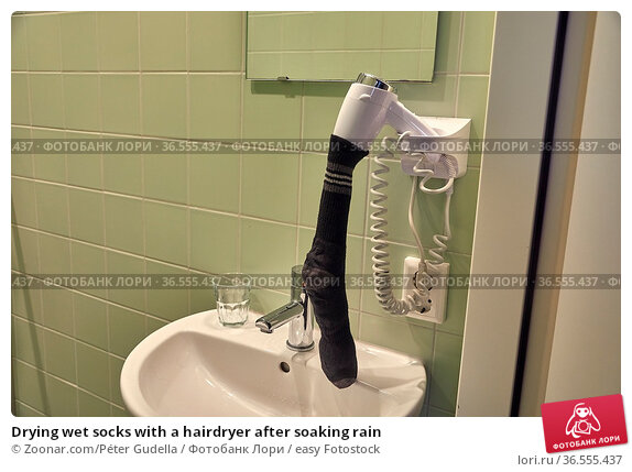 Drying wet socks with a hairdryer after soaking rain. Стоковое фото, фотограф Zoonar.com/Péter Gudella / easy Fotostock / Фотобанк Лори