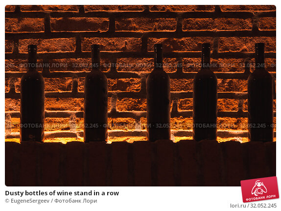 Dusty bottles of wine stand in a row. Стоковое фото, фотограф EugeneSergeev / Фотобанк Лори
