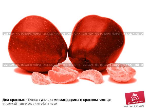 Два красных яблока с дольками мандарина в красном глянце, фото № 253429, снято 12 марта 2008 г. (c) Алексей Пантелеев / Фотобанк Лори