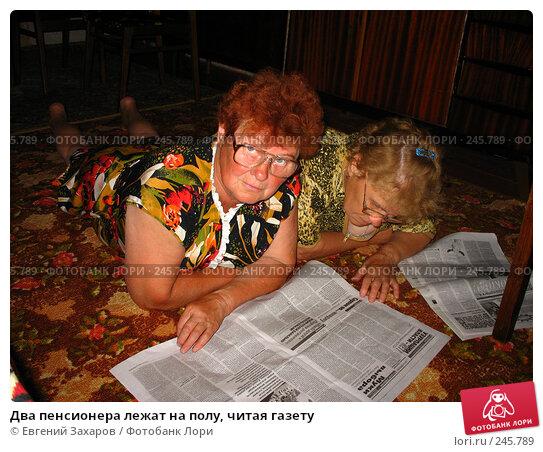 Два пенсионера лежат на полу, читая газету, фото № 245789, снято 26 июня 2006 г. (c) Евгений Захаров / Фотобанк Лори