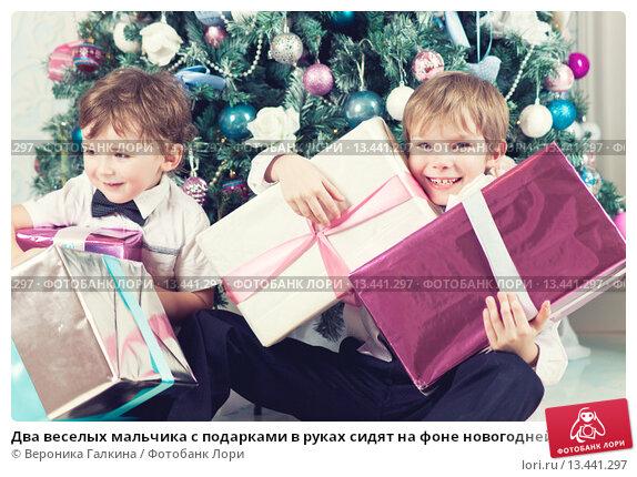 Купить «Два веселых мальчика с подарками в руках сидят на фоне новогодней елки», фото № 13441297, снято 26 декабря 2013 г. (c) Вероника Галкина / Фотобанк Лори