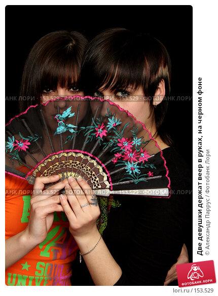 Две девушки держат веер в руках, на черном фоне, фото № 153529, снято 4 мая 2007 г. (c) Александр Паррус / Фотобанк Лори