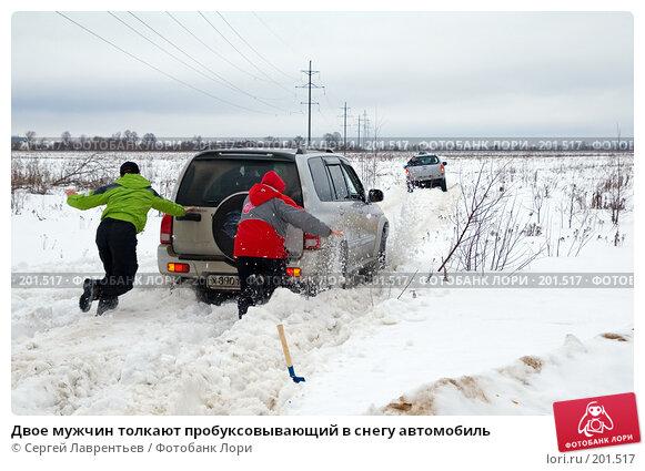 Двое мужчин толкают пробуксовывающий в снегу автомобиль, фото № 201517, снято 9 февраля 2008 г. (c) Сергей Лаврентьев / Фотобанк Лори