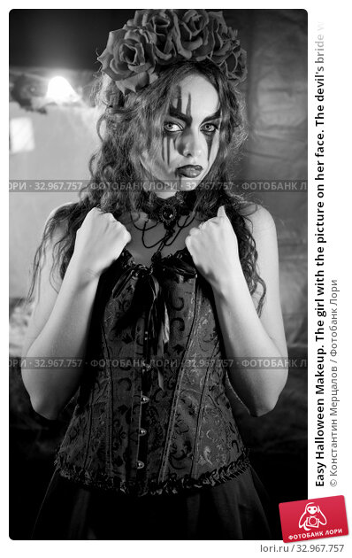 Easy Halloween Makeup. The girl with the picture on her face. The devil's bride with a wreath of red flowers on her head. The woman is wearing a black corset dress and black stockings. Стоковое фото, фотограф Константин Мерцалов / Фотобанк Лори