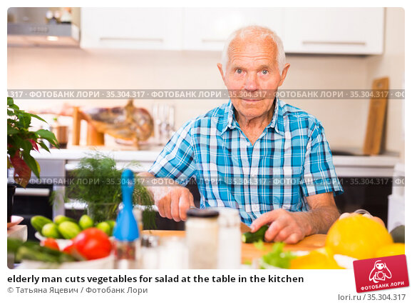 elderly man cuts vegetables for salad at the table in the kitchen. Стоковое фото, фотограф Татьяна Яцевич / Фотобанк Лори