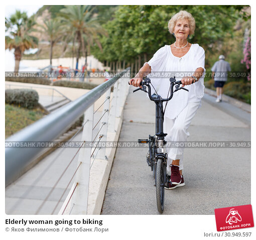 Купить «Elderly woman going to biking», фото № 30949597, снято 6 июля 2018 г. (c) Яков Филимонов / Фотобанк Лори