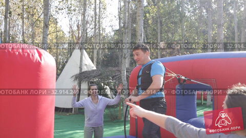 Купить «Emotional man tied with rope to his friend competing to collect hoops on inflatable ring», видеоролик № 32914249, снято 12 ноября 2019 г. (c) Яков Филимонов / Фотобанк Лори