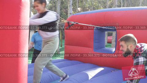 Emotional woman trying to put on hoop on log on inflatable playground, male friends watching. Стоковое видео, видеограф Яков Филимонов / Фотобанк Лори