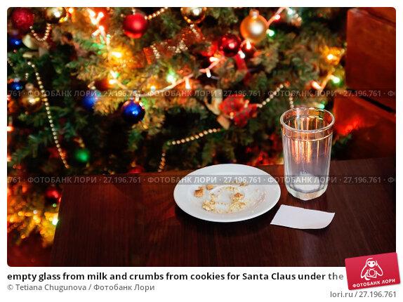 Купить «empty glass from milk and crumbs from cookies for Santa Claus under the Christmas tree with lights, close-up», фото № 27196761, снято 12 мая 2017 г. (c) Tetiana Chugunova / Фотобанк Лори