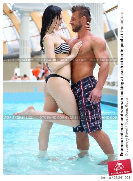 Купить «Enamoured man and woman looking at each other in pool at the aquapark», фото № 25841021, снято 28 февраля 2015 г. (c) Losevsky Pavel / Фотобанк Лори