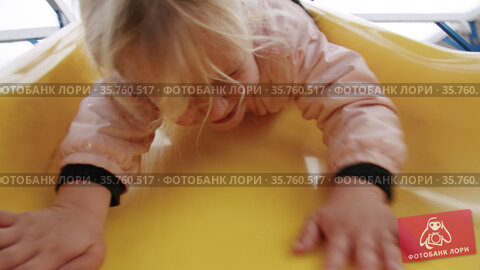 Excited little girl having fun on the slide in playground. Стоковое видео, видеограф Данил Руденко / Фотобанк Лори