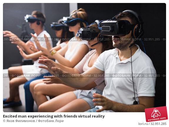 Excited man experiencing with friends virtual reality. Стоковое фото, фотограф Яков Филимонов / Фотобанк Лори