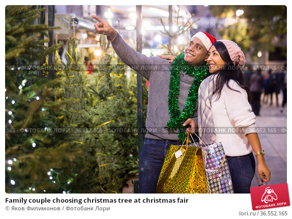 Family couple choosing christmas tree at christmas fair. Стоковое фото, фотограф Яков Филимонов / Фотобанк Лори