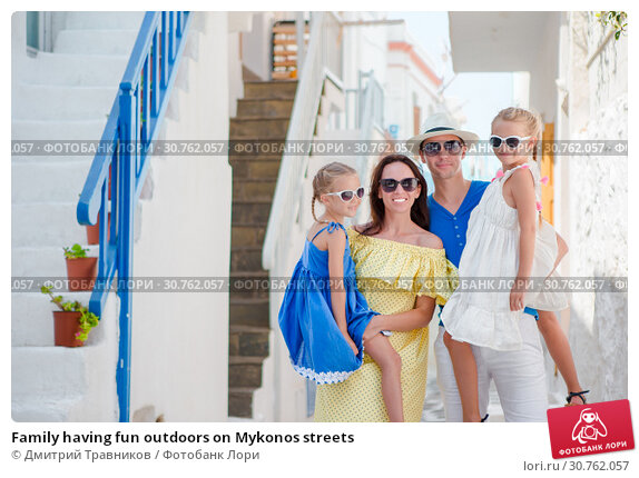 Купить «Family having fun outdoors on Mykonos streets», фото № 30762057, снято 21 августа 2016 г. (c) Дмитрий Травников / Фотобанк Лори
