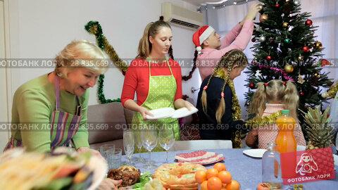 Купить «Family is preparing for celebration New Year together at home.», видеоролик № 28835669, снято 17 января 2018 г. (c) Яков Филимонов / Фотобанк Лори