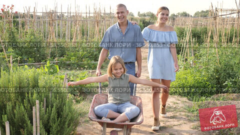Family of three resting in garden. Father carrying cart with his daughter in it. Стоковое видео, видеограф Яков Филимонов / Фотобанк Лори