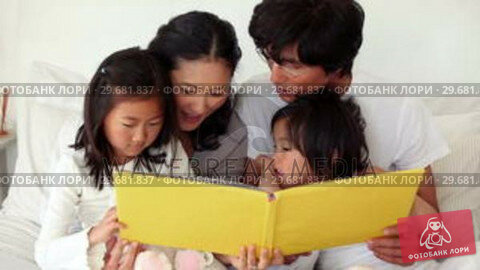 Купить «Family reading a book as they sit together», видеоролик № 29681837, снято 25 ноября 2011 г. (c) Wavebreak Media / Фотобанк Лори