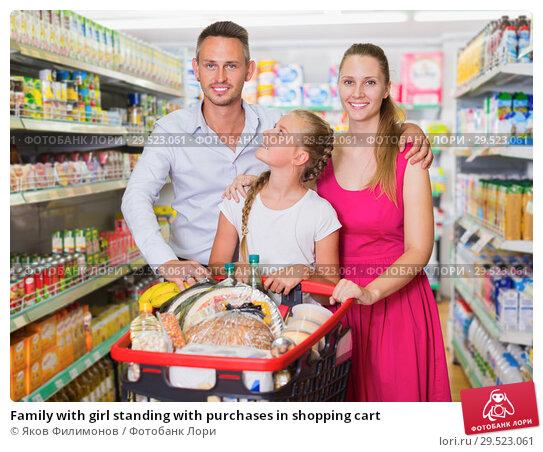 Купить «Family with girl standing with purchases in shopping cart», фото № 29523061, снято 11 июля 2017 г. (c) Яков Филимонов / Фотобанк Лори
