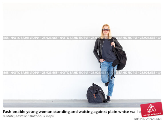 Купить «Fashionable young woman standing and waiting against plain white wall on the station whit travel bag by her side.», фото № 28926665, снято 21 августа 2018 г. (c) Matej Kastelic / Фотобанк Лори