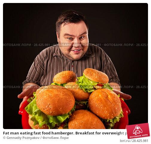 Купить «Fat man eating fast food hamberger. Breakfast for overweight person.», фото № 28425981, снято 24 марта 2017 г. (c) Gennadiy Poznyakov / Фотобанк Лори