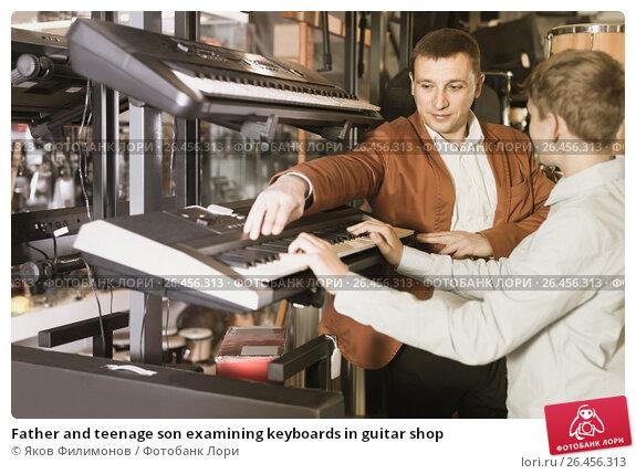 Купить «Father and teenage son examining keyboards in guitar shop», фото № 26456313, снято 29 марта 2017 г. (c) Яков Филимонов / Фотобанк Лори