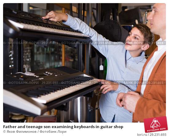 Купить «Father and teenage son examining keyboards in guitar shop», фото № 29231693, снято 29 марта 2017 г. (c) Яков Филимонов / Фотобанк Лори