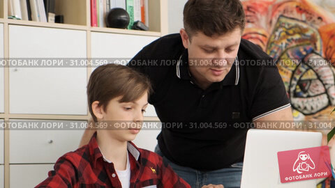 Father watches on the screen of the laptop searching the nessesary task helping his son to prepare for school slow motion. Стоковое видео, видеограф Denis Mishchenko / Фотобанк Лори