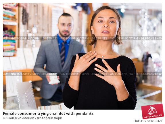 Female consumer trying chainlet with pendants. Стоковое фото, фотограф Яков Филимонов / Фотобанк Лори
