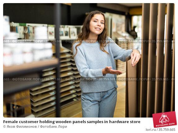 Female customer holding wooden panels samples in hardware store. Стоковое фото, фотограф Яков Филимонов / Фотобанк Лори