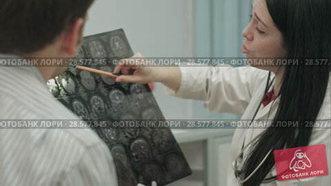 Купить «Female doctor in clinic show x-rays to male patient.», видеоролик № 28577845, снято 24 ноября 2015 г. (c) Vasily Alexandrovich Gronskiy / Фотобанк Лори