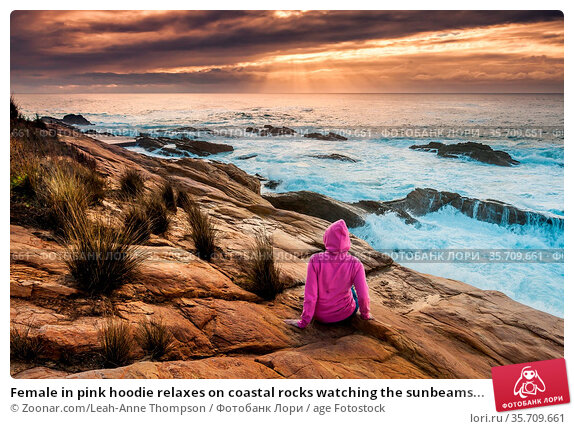 Female in pink hoodie relaxes on coastal rocks watching the sunbeams... Стоковое фото, фотограф Zoonar.com/Leah-Anne Thompson / age Fotostock / Фотобанк Лори