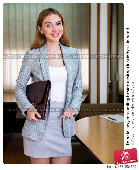 Female lawyer standing beside desk with briefcase in hand. Стоковое фото, фотограф Яков Филимонов / Фотобанк Лори