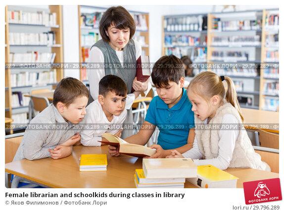 Купить «Female librarian and schoolkids during classes in library», фото № 29796289, снято 19 декабря 2018 г. (c) Яков Филимонов / Фотобанк Лори