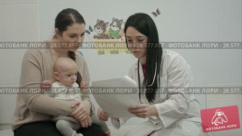 Купить «female pediatrician doctor shows some papers to woman with small baby», видеоролик № 28577857, снято 24 ноября 2015 г. (c) Vasily Alexandrovich Gronskiy / Фотобанк Лори