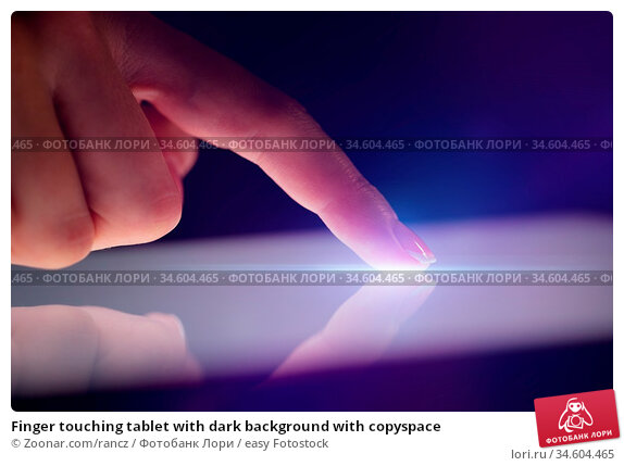 Finger touching tablet with dark background with copyspace. Стоковое фото, фотограф Zoonar.com/rancz / easy Fotostock / Фотобанк Лори