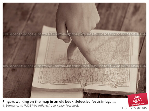 Fingers walking on the map in an old book. Selective focus image.... Стоковое фото, фотограф Zoonar.com/RUDE / easy Fotostock / Фотобанк Лори