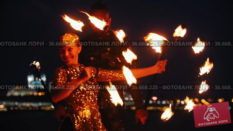 Fire show - woman and man in a shiny clothes performing with fire torches on the night beach. Стоковое видео, видеограф Константин Шишкин / Фотобанк Лори