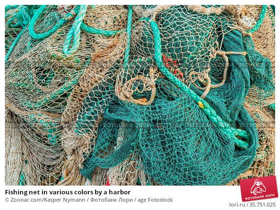 Fishing net in various colors by a harbor. Стоковое фото, фотограф Zoonar.com/Kasper Nymann / age Fotostock / Фотобанк Лори