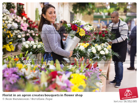 Florist in an apron creates bouquets in flower shop. Стоковое фото, фотограф Яков Филимонов / Фотобанк Лори